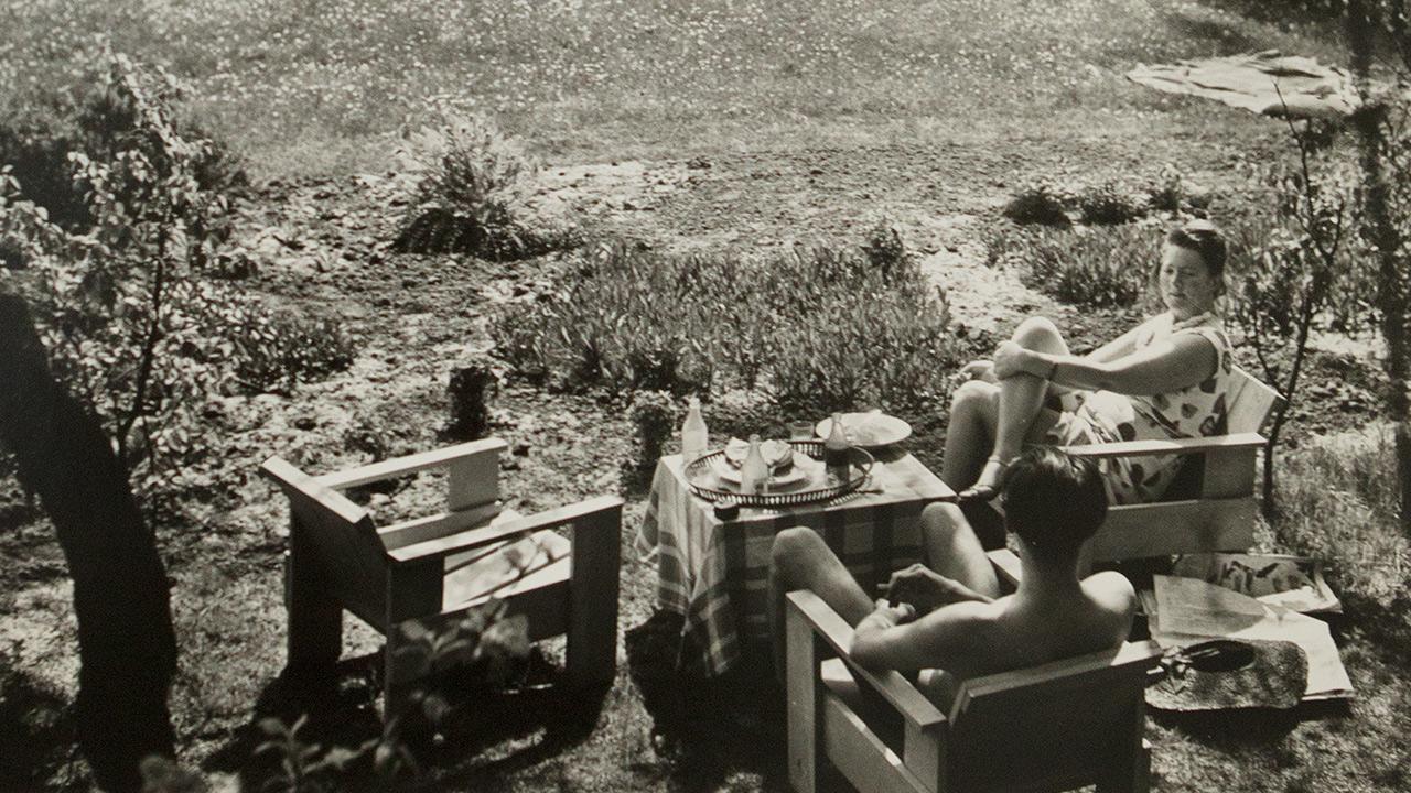 Charley-Toorop-en-John-Fernhout-zittend-op-Rietvelds-kratstoelen-in-de-tuin-met-uitzicht-op-De-Vlerken.jpg